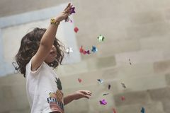 Kleines Mädchen, das mit bunten Konfettis spielt lizenzfreies stockbild