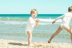 Kleines Mädchen, das mit dem Sand auf dem Strand spielt Stockfotos