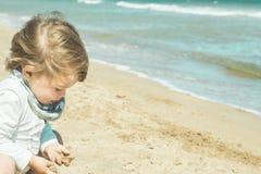 Kleines Mädchen, das mit dem Sand auf dem Strand spielt Lizenzfreies Stockfoto