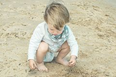 Kleines Mädchen, das mit dem Sand auf dem Strand spielt Lizenzfreie Stockfotos