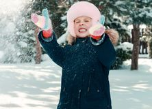 Kleines Mädchen, das mit dem Schnee spielt Stockfotos