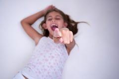 Kleines Mädchen, das mit dem zeigenden und lachenden Finger liegt Stockbilder