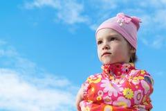 Kleines Mädchen, das mit den gefalteten Händen, starrend in den Abstand steht an Stockfotografie