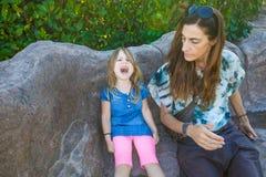 Kleines Mädchen, das mit der schauenden und schreienden Mutter sitzt Lizenzfreie Stockbilder