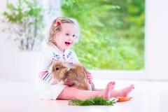 Kleines Mädchen, das mit einem Häschen spielt Lizenzfreie Stockfotografie