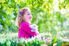 Kleines Mädchen, das mit einem Kaninchen spielt Stockbild