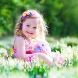 Kleines Mädchen, das mit einem Kaninchen spielt Lizenzfreie Stockfotografie