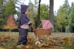 Kleines Mädchen, das mit einem Pram im Park spielt lizenzfreie stockfotografie