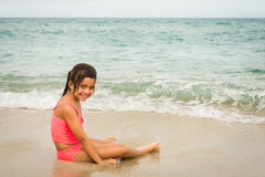 Kleines Mädchen, das mit einem Starfish auf dem Strand spielt Stockbild