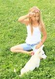 Kleines Mädchen, das mit einem Welpen spielt Lizenzfreies Stockbild