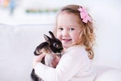 Kleines Mädchen, das mit einem wirklichen Haustierkaninchen spielt Stockbild