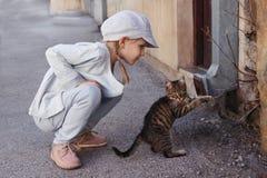 Kleines Mädchen, das mit einer Katze spielt Lizenzfreies Stockbild