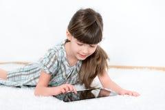 Kleines Mädchen, das mit Apfel ipad Tablette spielt Lizenzfreie Stockfotografie