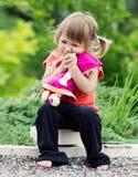 Kleines Mädchen, das mit einer Puppe spielt Lizenzfreie Stockfotografie
