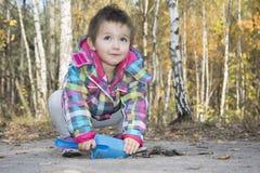 Kleines Mädchen, das mit einer Schaufel gräbt den Boden im autu spielt Lizenzfreie Stockbilder