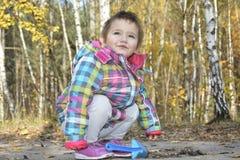 Kleines Mädchen, das mit einer Schaufel gräbt den Boden im autu spielt Stockbild