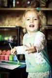 Kleines Mädchen, das mit Farben spielt Lizenzfreies Stockfoto