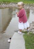 Kleines Mädchen, das mit hölzernem Boot im Wasser spielt Stockfotos