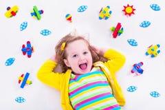 Kleines Mädchen, das mit hölzernem Flugzeug spielt Stockfoto