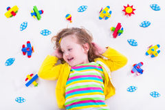 Kleines Mädchen, das mit hölzernem Flugzeug spielt Lizenzfreie Stockfotos