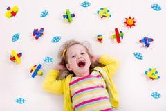 Kleines Mädchen, das mit hölzernem Flugzeug spielt Lizenzfreies Stockfoto