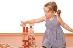 Kleines Mädchen, das mit hölzernen Blöcken spielt stockbilder
