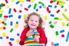 Kleines Mädchen, das mit hölzernen Blöcken spielt Lizenzfreie Stockfotos