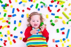 Kleines Mädchen, das mit hölzernen Blöcken spielt Lizenzfreies Stockbild