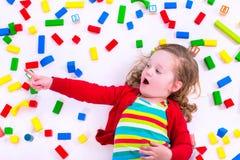 Kleines Mädchen, das mit hölzernen Blöcken spielt Lizenzfreie Stockbilder