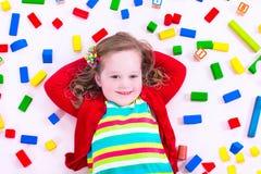 Kleines Mädchen, das mit hölzernen Blöcken spielt Stockbild