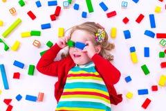 Kleines Mädchen, das mit hölzernen Blöcken spielt Lizenzfreies Stockfoto