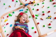 Kleines Mädchen, das mit hölzernen Zügen spielt Lizenzfreies Stockbild