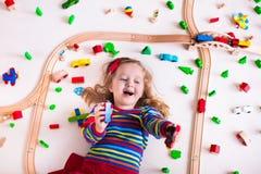 Kleines Mädchen, das mit hölzernen Zügen spielt Stockfotografie