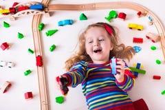 Kleines Mädchen, das mit hölzernen Zügen spielt Stockfotos