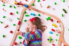 Kleines Mädchen, das mit hölzernen Zügen spielt Lizenzfreie Stockbilder