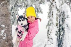 Kleines Mädchen, das mit heiserem Hund auf dem Schnee spielt lizenzfreie stockfotografie