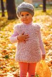 Kleines Mädchen, das mit Herbstblättern spielt Stockfoto