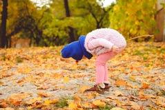 Kleines Mädchen, das mit Herbstblättern spielt Lizenzfreie Stockfotografie