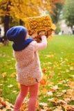 Kleines Mädchen, das mit Herbstblättern spielt Stockbild