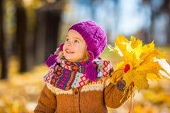 Kleines Mädchen, das mit Herbstblättern spielt Stockfotos