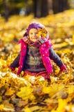 Kleines Mädchen, das mit Herbstblättern spielt Lizenzfreie Stockbilder