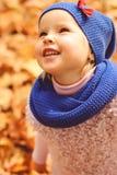 Kleines Mädchen, das mit Herbstlaub im Park spielt Stockfoto