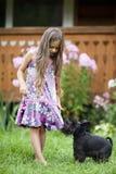 Kleines Mädchen, das mit ihrem Hund spielt Stockbild