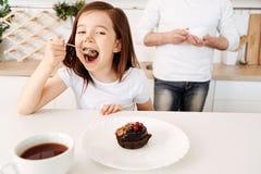 Kleines Mädchen, das mit ihrem Kuchen erfreut schaut Stockbild