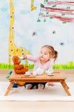 Kleines Mädchen, das mit ihrem Teddybären an der Teeparty spielt Stockbild