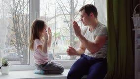 Kleines Mädchen, das mit ihrem Vater am O.K. spielt stock footage