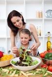 Kleines Mädchen, das mit ihrer Mutter kocht Lizenzfreie Stockfotos