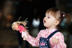 Kleines Mädchen, das mit ihrer Vechelie Puppe spielt. Stockbilder