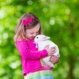 Kleines Mädchen, das mit Kaninchen spielt Stockfotografie