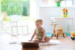 Kleines Mädchen, das mit Laptop auf dem Boden spielt Stockfoto